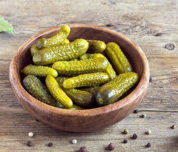 Pickles. Bowl of pickled gherkins (cucumbers) over rustic wooden background close up.